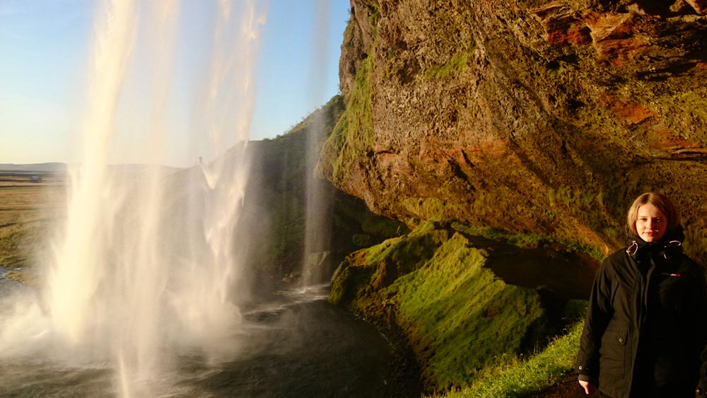 Seljalandsfoss waterfall walking behind in the sunset
